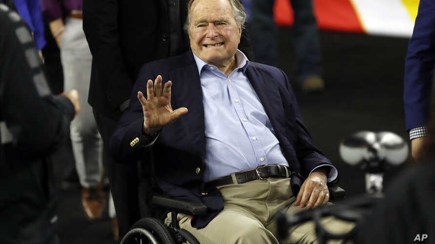 FILE - Former president George H. W. Bush waves as he arrives at a sports stadium in Houston, Texas, April 2, 2016.