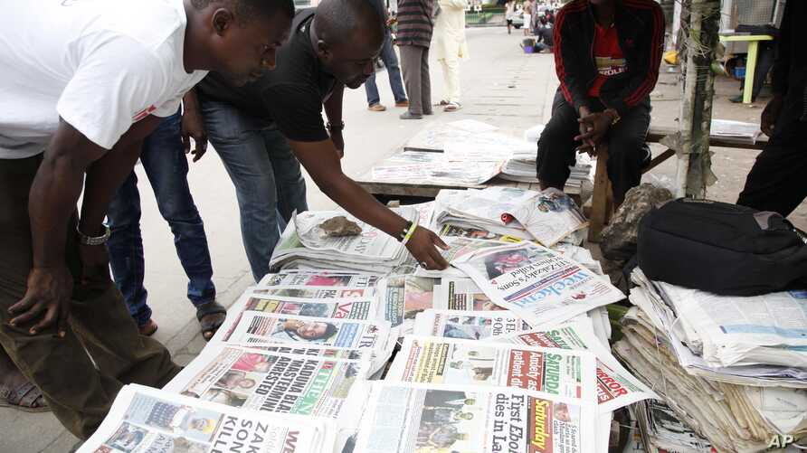 Men read newspapers on a street with headlines about Ebola Virus killing a Liberian in Lagos, Nigeria, July 26, 2014.