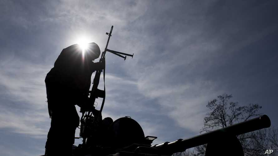 A Ukrainian soldier stands atop a military vehicle near Artemivsk, eastern Ukraine, Monday, Feb. 23, 2015.