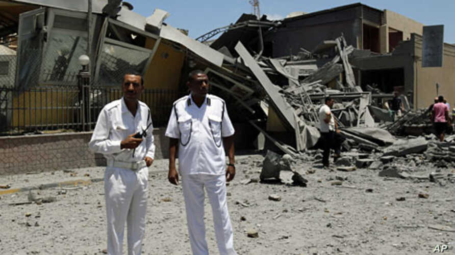 Libyan policemen stand next to a destroyed building that officials said was struck by a NATO airstrike in Tripoli, June 16, 2011