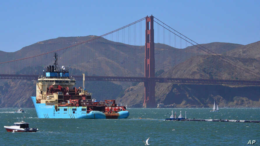 FILE - A ship tows The Ocean Cleanup's first buoyant trash-collecting device toward the Golden Gate Bridge in San Francisco en route to the Pacific Ocean, Sept. 8, 2018.