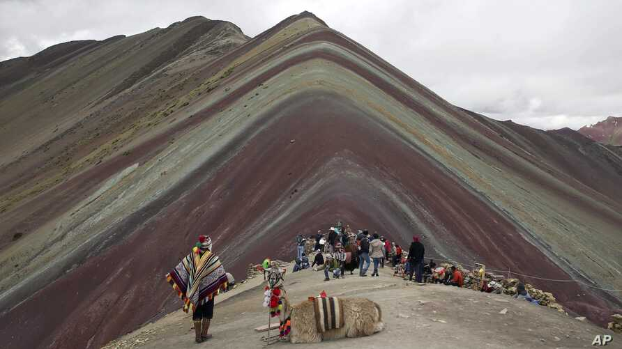 An Andean man rests with his llama while tourists take in the natural wonder of Rainbow Mountain in Pitumarca, Peru, March 2, 2018.