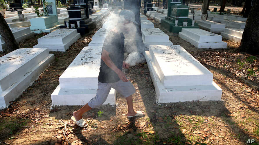 FILE - In this photo taken April 18, 2015, Nguyen Van Ba helps visitors place sticks of incense into graves at the former South Vietnamese military cemetery, in Binh Duong province, outside of Ho Chi Minh City, Vietnam.