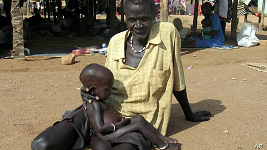 Amid famine in the Horn of African, World Food Program officials are now calling for increased food aid in Zimbabwe. Above, Man and malnourished grandson at food clinic in Sudan, Sept. 11 2005 (file photo).