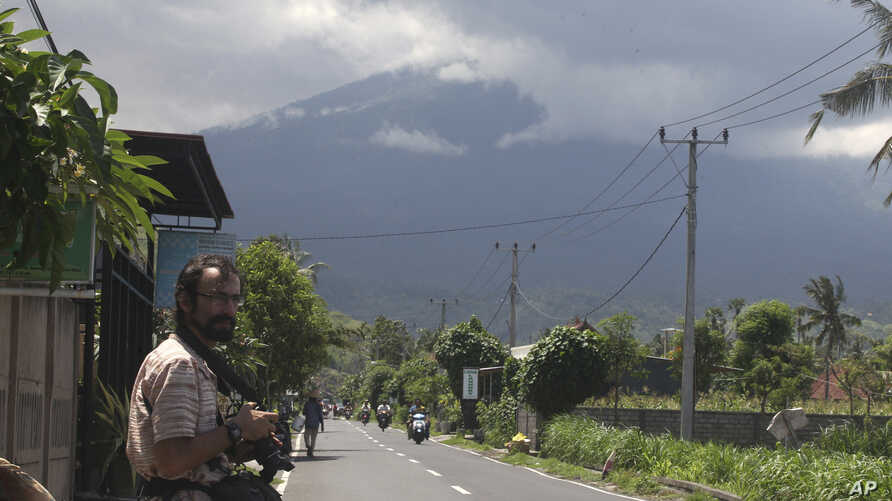 Mark Levitin, 39, a freelance photographer from Russi,a stands on a street with a backdrop of the Mount Agung volcano covered by cloud in Karangasem, Bali, Indonesia, Nov. 29, 2017.