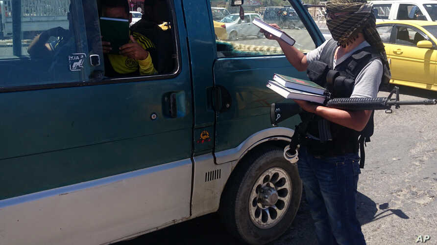 A fighter with the Islamic State of Iraq and the Levant distributes a copy of the Quran, Islam's holy book, to a driver in central northern city of Mosul, Iraq, June 22, 2014.