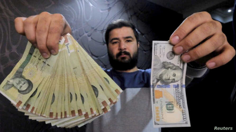 FILE PHOTO - A money changer poses for the camera with a U.S dollar, right, and the amount being given when converting it into Iranian rials at a currency exchange shop in Tehran's business district, Iran, Jan. 20, 2016.