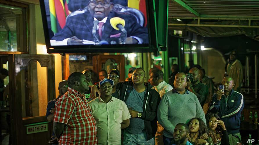 Zimbabweans watch a televised address to the nation by President Robert Mugabe at a bar in downtown Harare, Zimbabwe, Nov. 19, 2017.
