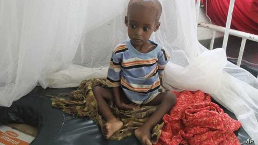 A malnourished child from southern Somalia sits on a bed at Banadir hospital in Mogadishu, Somalia, August 1, 2011