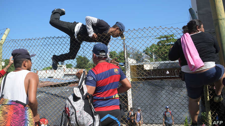 Salvadorean migrants climb and jump over a fence to get to the Guatemala-Mexico international border bridge in Ciudad Tecun Uman, Guatemala, on Nov. 2, 2018.