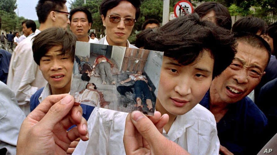 FILE- In this file photo take June 5, 1989, people on Chang'an Boulevard hold up a photo that they described as dead victims of the violence against pro-democracy protesters on Tiananmen Square, Beijing. Hundreds had been killed in the early morning ...