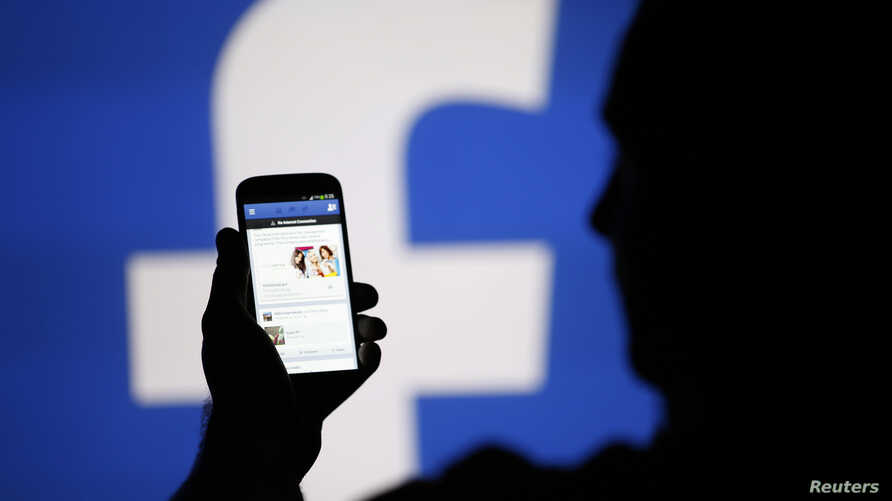 A man is silhouetted against a video screen with an Facebook logo as he poses with an Samsung S4 smartphone in this photo illustration taken in the central Bosnian town of Zenica, August 14, 2013.