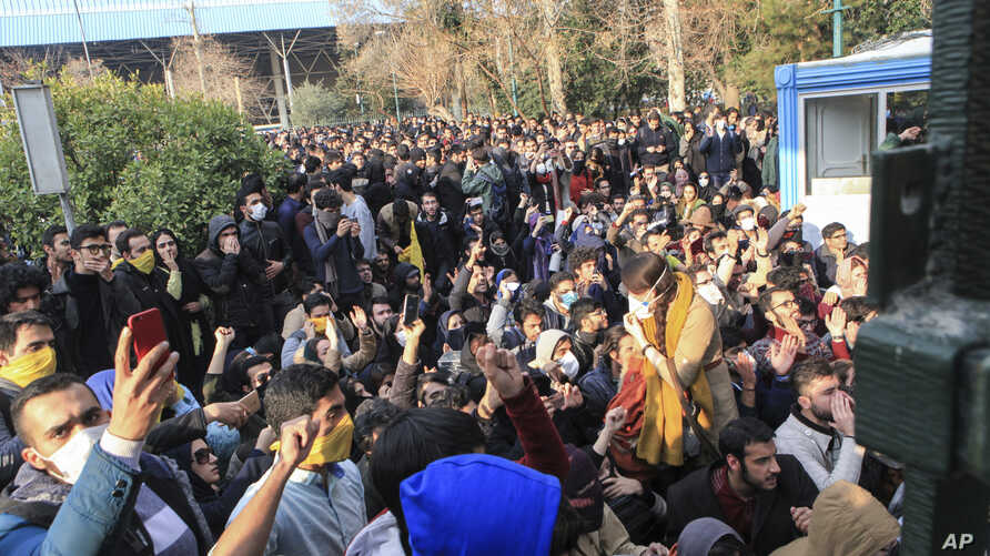 In this Saturday, Dec. 30, 2017 file photo taken by an individual not employed by the Associated Press and obtained by the AP outside Iran, university students attend a protest inside Tehran University while anti-riot Iranian police prevent them to j
