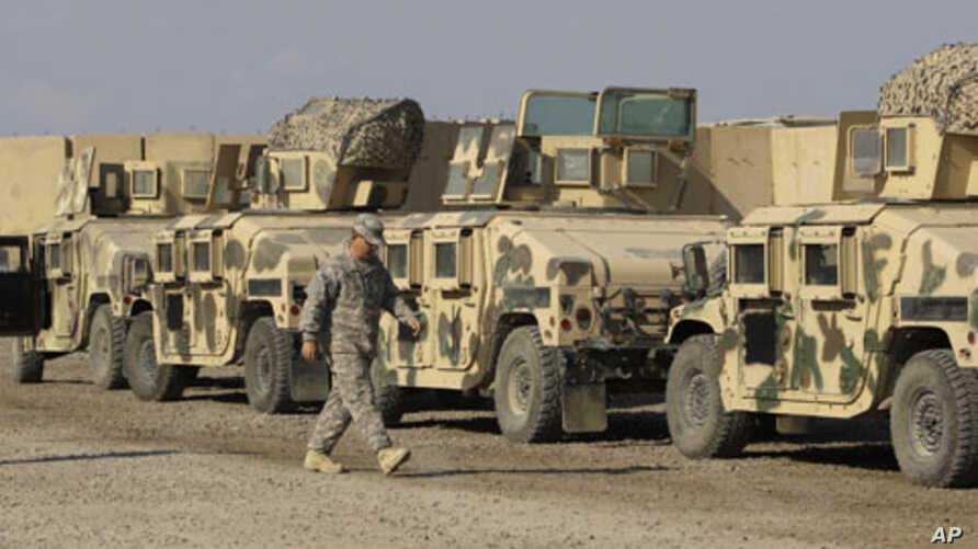 U.S. army soldiers walk past military armored vehicles ready to be shipped out of Iraq at Camp Victory Baghdad, Iraq, November 7, 2011.