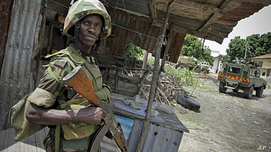 A Ugandan soldier serving with the African Union Mission in Somalia stands guard during the removal of a haul of 155mm artillery shells that were found in a house deep inside a former al-Shabab stronghold in the Somali capital Mogadishu, August 12, 2