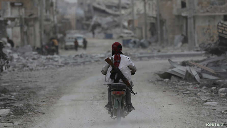 A man drives a motorcycle while carrying his weapon near damaged buildings in the northern Syrian town of al-Bab, Syria March 1, 2017.