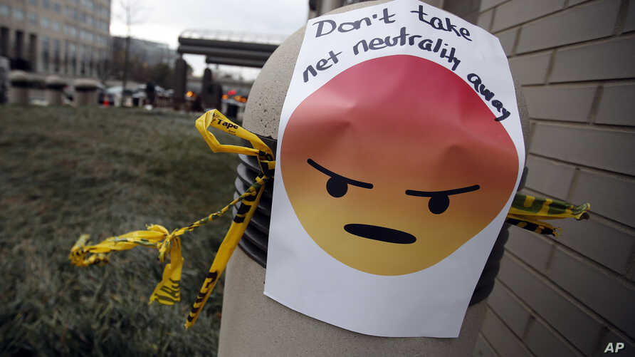 """FILE - A sign with an emoji that reads """"Don't take net neutrality away"""" is posted outside the Federal Communications Commission (FCC), in Washington, Dec. 14, 2017."""