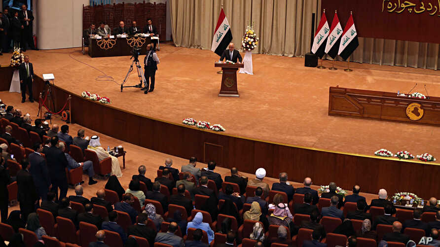 Iraq Prime Minister Haider al-Abadi, center, addresses a newly elected parliament during its first session in Baghdad, Sept. 3, 2018.
