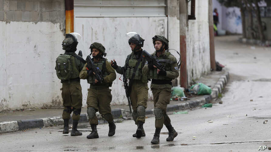 Members of Israeli armed forces patrol through the streets of the West Bank city of Jenin, Jan. 18, 2018. Israeli police say special forces killed a Palestinian gunman in the West Bank who allegedly killed an Israeli in a drive-by shooting earlier th