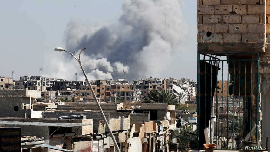 Smoke rises near the stadium where the Islamic State militants are holed up after an air strike by coalition forces at the frontline, in Raqqa, Oct. 12, 2017.
