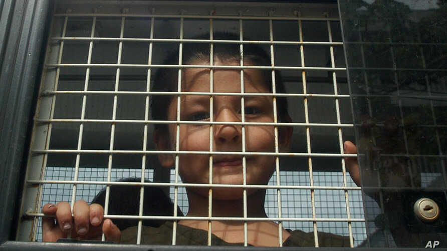 FILE - Ethnic Uighur Muslim boy stands inside a police van in Khlong Hoi Khong of southern Songkhla province, Thailand. He was in a group of 200 people rescued from a human trafficking camp.