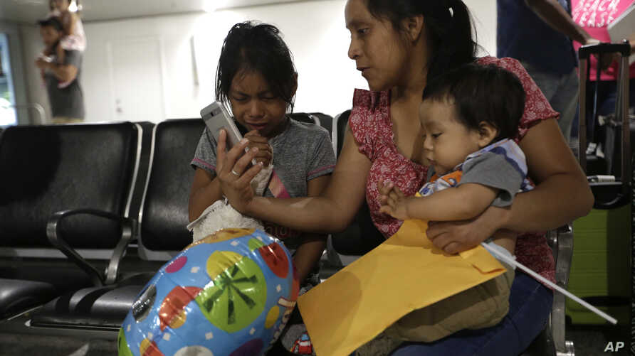 Buena Ventura Martin-Godinez, center, holds her son Pedro, right, as she is reunited with her daughter Janne, left, at Miami International Airport, July 1, 2018, in Miami, Florida. Martin crossed the border into the United States from Mexico in May w