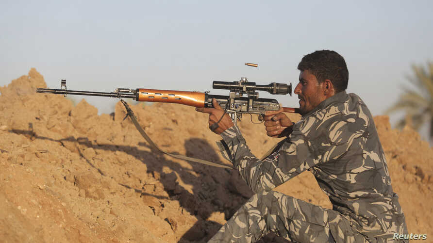 A Shiite fighter takes aim during a patrol in Jurf al-Sakhar, Iraq, which Iraqi security forces retook from Islamic State militants, Oct. 25, 2014.