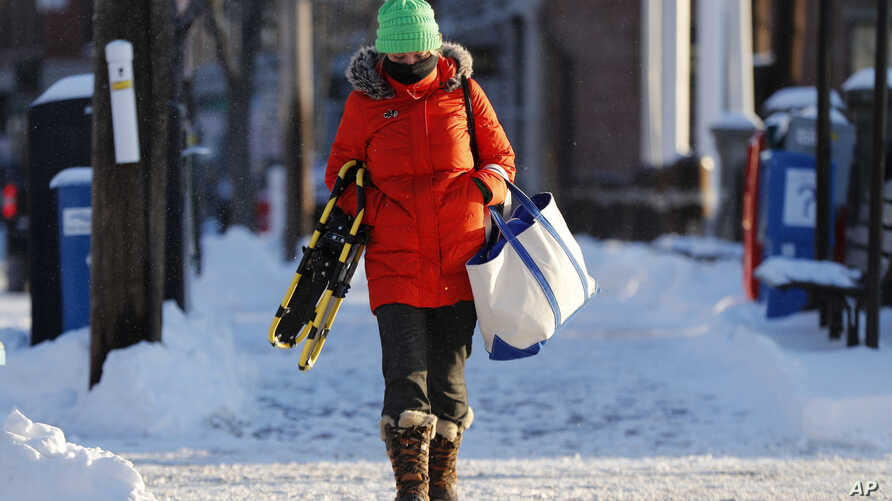Lauren Webster is bundled up as she makes her way to work on a bitter cold morning, Jan. 31, 2019, in Portland, Maine.