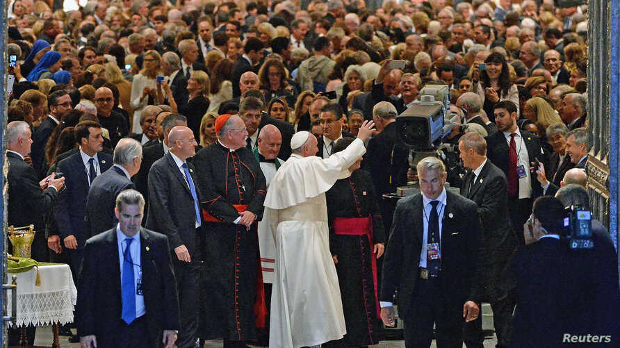 Pope Francis waves to gathered worshipers as he leaves St. Patrick's Cathedral after presiding over an evening prayer service, in New York, September 24, 2015.