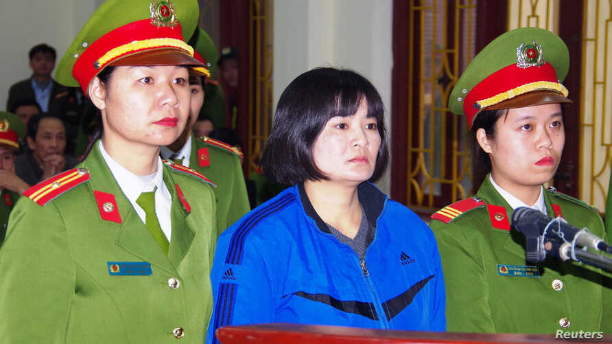 Vietnamese prominent activist Tran Thi Nga stands between police in the dock during her appeal trial in Phu Ly city, Vietnam Dec. 22, 2017.