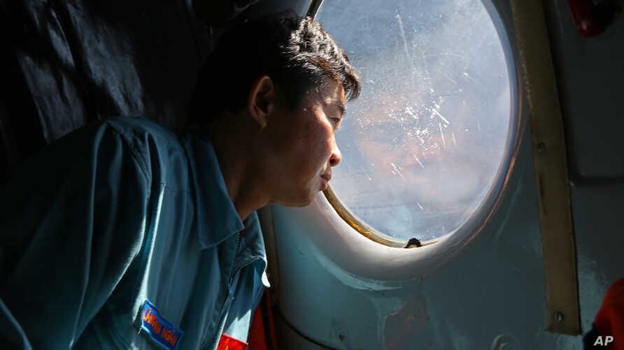 Officer Lang Van Ngan of the Vietnam Air Force looks out the window onboard a flying AN-26 Soviet made aircraft during a search operation for the missing Malaysia Airlines flight MH370 plane over the southern sea between Vietnam and Malaysia, March 1
