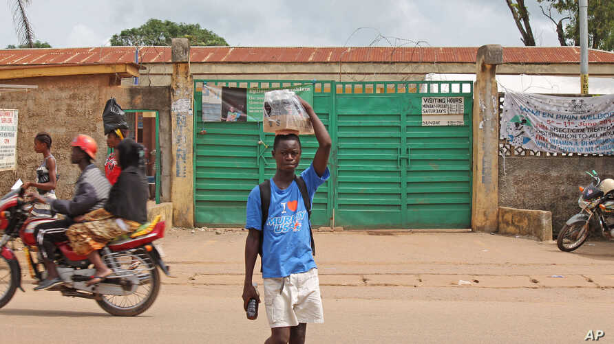 A boy, (c) selling soft drinks walk past a clinic taking care of Ebola patients in the Kenema District on the outskirts of Kenema, Sierra Leone.  Liberia President Ellen Johnson Sirleaf has closed some border crossings and ordered strict quarantines
