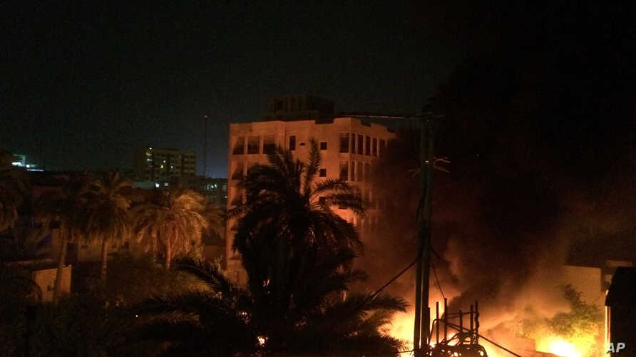 A fire erupts as smoke billows from the site of a car bomb, April 28, 2017, in Baghdad. Iraqi police and hospital officials said a car bomb at a police station in central Baghdad killed four and wounded eight late Friday night.