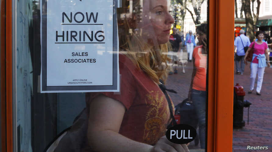 FILE - A woman walks past a 'Now Hiring' sign as she leaves the Urban Outfitters store at Quincy Market in Boston, Massachusetts, Sept. 5, 2014.