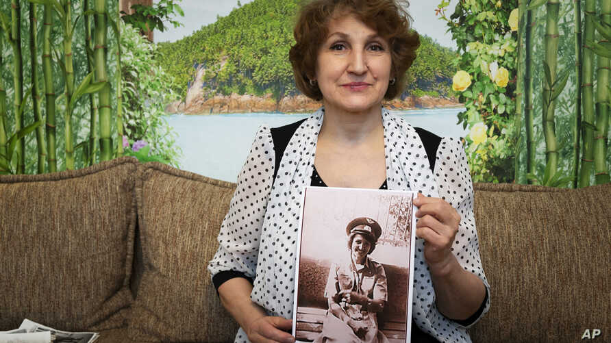 FILE - Tatyana Rybalchenko, who worked as a nurse during the Soviet campaign in Afghanistan between 1986 and 1988, holds a photo of her taken in June 1986 in Kabul, Afghanistan, during her interview in Moscow, Russia, Feb. 10, 2019.