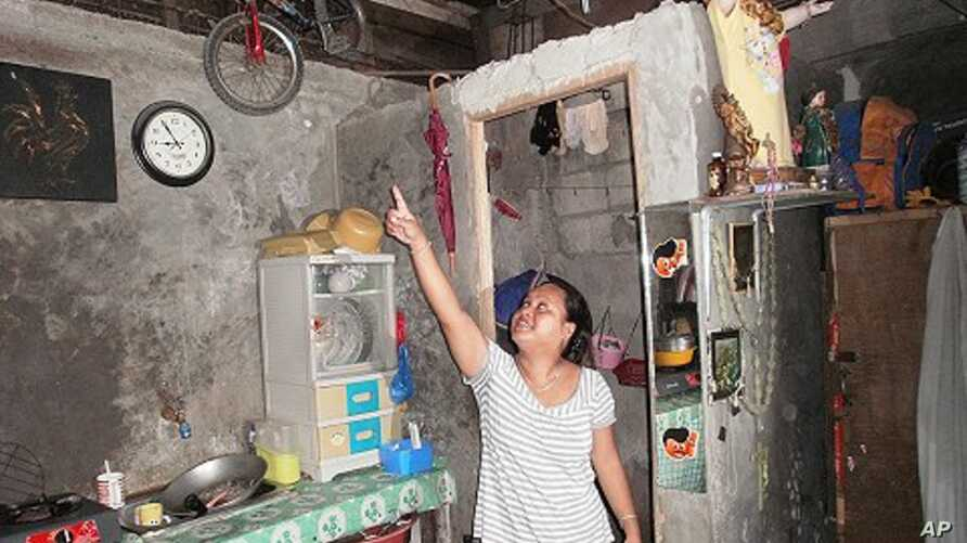 Sheila Royeras admires the soda bottle solar bulbs that were installed in her shanty home. The bulbs are made out of a soda bottle, purified water and some bleach. San Juan City, Metropolitan Manila, Philippines,  November 18, 2011.