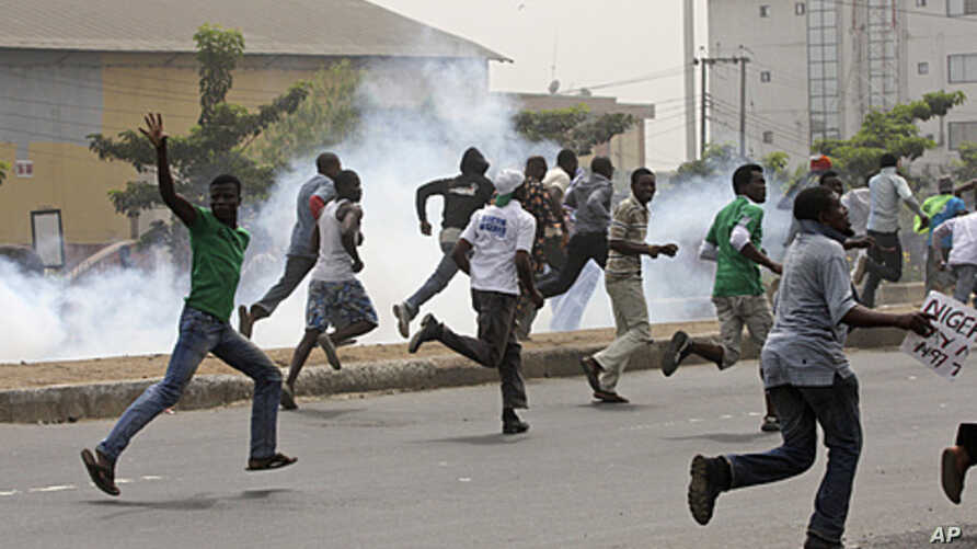 Protesters run away from tear gas fired by police officers during a demonstration against spiraling fuel prices in Lagos, Nigeria, January 16, 2012.