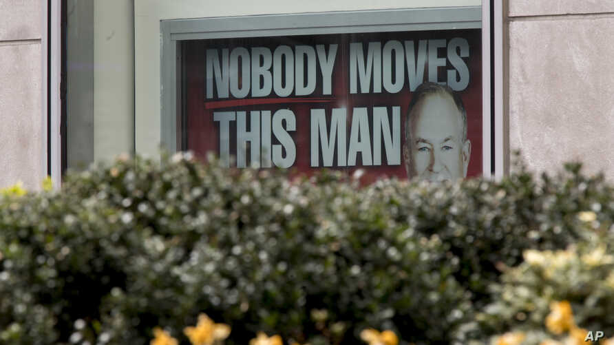 A poster featuring Bill O'Reilly is displayed at the News Corp. headquarters building in Midtown Manhattan, April 19, 2017. Bill O'Reilly has lost his job at Fox News Channel following reports that five women had been paid millions of dollars to keep