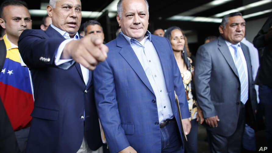 The leader of Venezuela's ruling socialist party Diosdado Cabello, center, accompanied by fellow delegate Pedro Carreno, left, leaves the General Prosecutors office in Caracas, Aug. 16, 2017. Cabello is alleging that the husband and close aides of ou