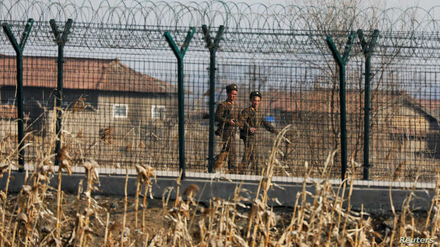 North Korean soldiers patrol behind a border fence near the North Korean town of Sinuiju, March 31, 2017.