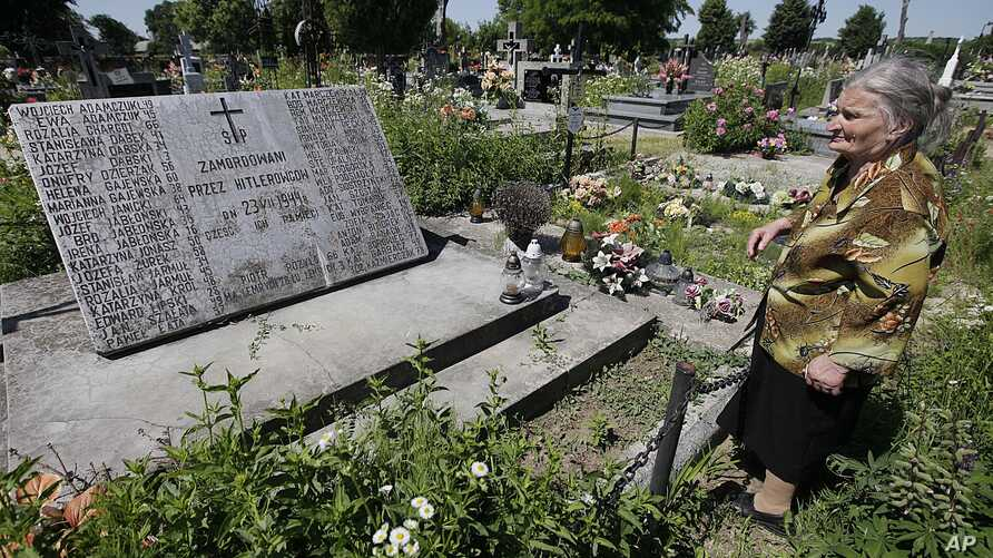FILE - A woman stands near a mass grave and a monument in the village of Chlaniow, Poland, that holds the bodies of Poles killed in a 1944 attack on the village by the Nazi SS-led Ukrainian Self Defense Legion, June 19, 2013.