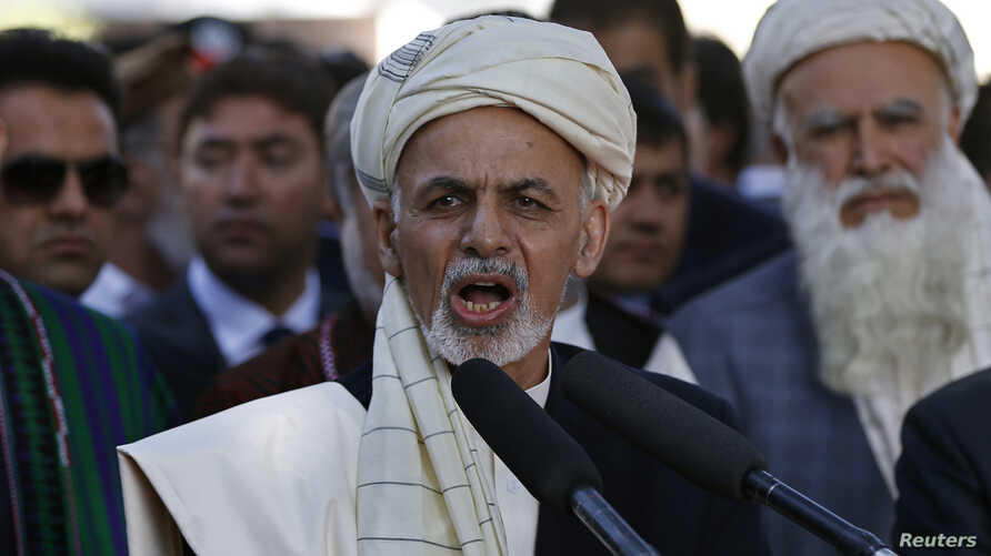 FILE - Afghanistan's President Ashraf Ghani (C) talks with the media after Eid al-Adha prayers at the presidential palace in Kabul.