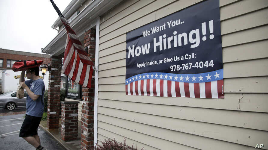A sign advertising employment hangs outside a restaurant in Middleton, Massachusetts, July 24, 2017.