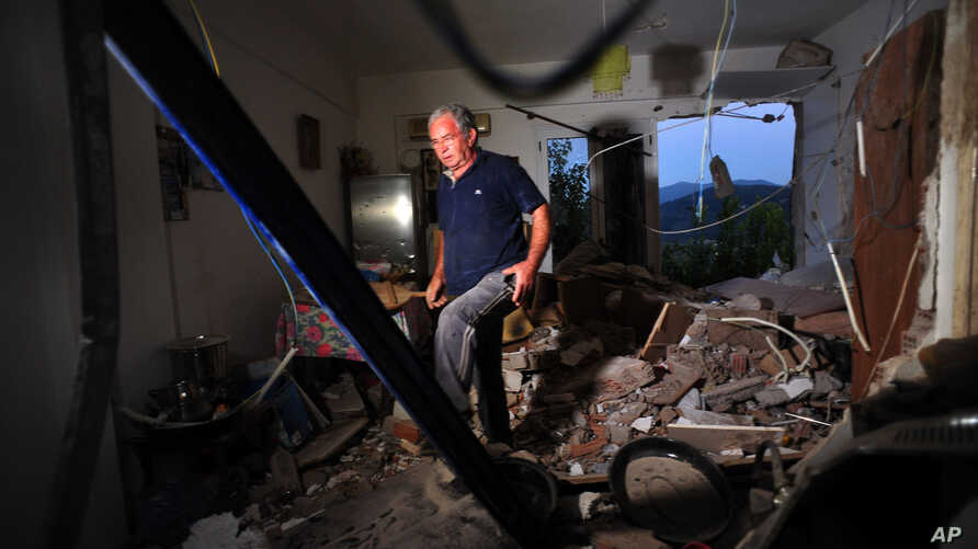 A man walks inside a destroyed house after an earthquake at the village of Pothi on the western Greek island of Lefkada, Nov. 17, 2015.