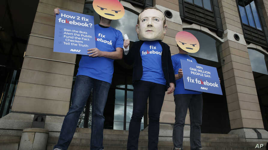 FILE - A protester wearing a mask with the face of Facebook founder Mark Zuckerberg is flanked by two fellow activists wearing angry face emoji masks, during a protest against Facebook policies, in London, Britain, April 26, 2018.