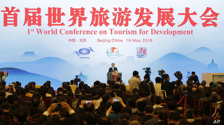China's Premier Li Keqiang, center, delivers a speech at the First World Conference on Tourism for Development at the Great Hall of the People in Beijing Thursday, May 19, 2016.