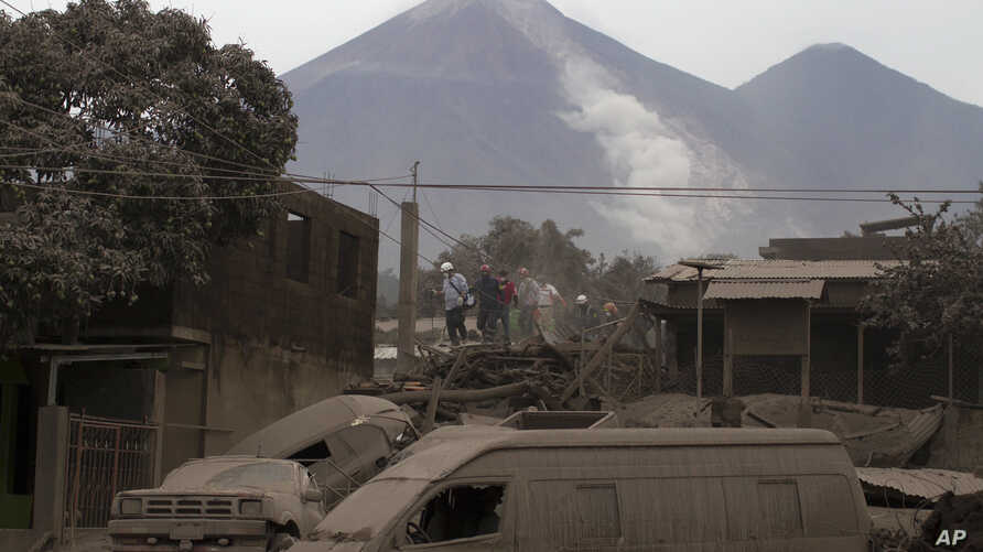 """Rescue workers walk on rooftops in Escuintla, Guatemala, Monday, June 4, 2018, blanketed with heavy ash spewed by the Volcan de Fuego, or """"Volcano of Fire,"""" pictured in the background, left center. A fiery volcanic eruption in south-central Guatemala"""