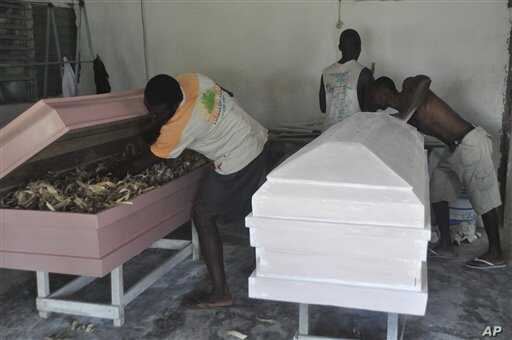 In this photo taken Wednesday, Oct. 22, 2014. A carpenter makes new caskets for sale in New Kru in Monrovia, Liberia. Even as Liberians get sick and die of Ebola, many beds in treatment centers are empty because of the government's order that the bod