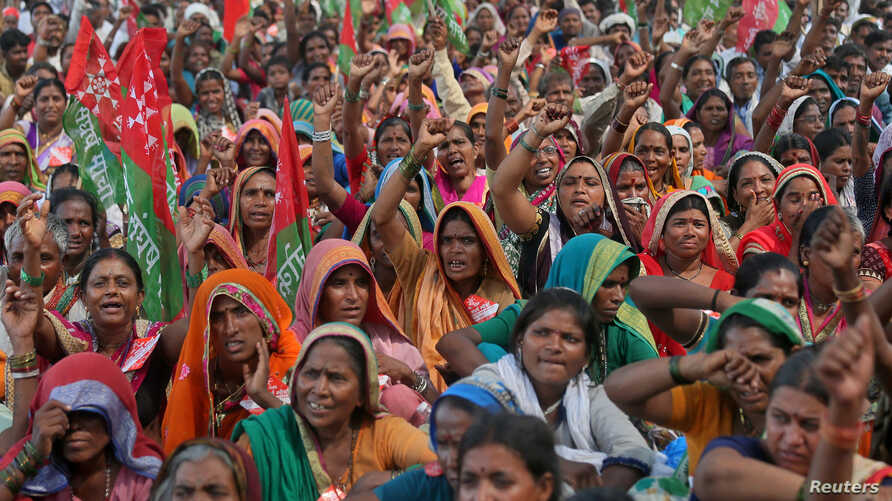 Farmers wave flags and shout slogans during a protest rally demanding loan waivers and the transfer of forest lands to villagers who have farmed there for decades, in Mumbai, India, Nov. 22, 2018.