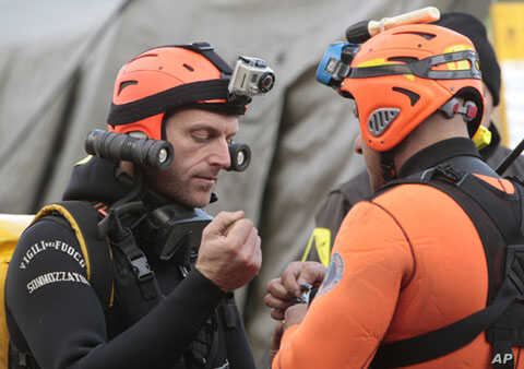 Italian divers chat as they prepare to head out to the cruise ship Costa Concordia, as it lays on its side after running aground off the tiny Tuscan island of Giglio, Italy, January 19, 2012.